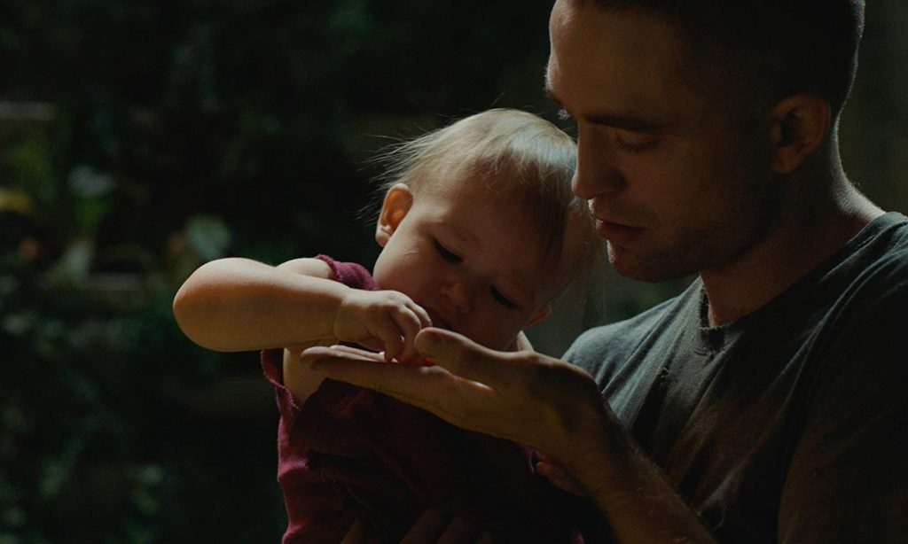 Monte (Robert Pattinson) holds his baby daughter in High Life (2018).